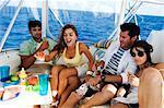 Zwei Paare genießen Bier und Früchte in einer tourboat
