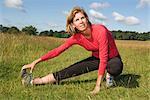 Femme qui s'étend de la jambe dans le champ
