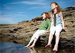 2 girls putting feet in cold rock pool