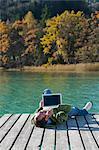 Man Lying on Dock, Using Laptop, Fuschlee, Fuschl am See, Salzkammergut, Salzburger Land, Austria
