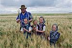 Hutterite Man and Girls Standing in Wheat Field, Silver Sage Colony, Alberta, Canada
