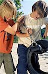 Deux garçons, tirant sur les chaînes d'un terrain de jeu en caoutchouc pneu-Swing - Fun - constant - loisir-
