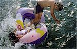 Deux garçons sauter d'un canot à la même heure - Fun - jeunesse - lac