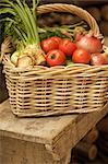 Nahaufnahme von Weidenkorb gefüllt mit Mischgemüse auf einer Holzbank