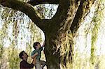 Father helping son climb a tree