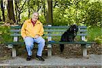 Un homme assis avec son chien sur un park bench, Prospect Park, Brooklyn, New York, Etats-Unis