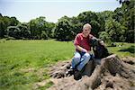 Un homme assis avec son chien dans un parc, Prospect Park, Brooklyn, New York, USA