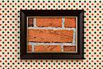 Une photo encadrée d'une brique mur accrocher sur un mur de papier peint