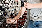 Detail of a man repairing a bike