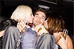 Women Kissing Man in Back of Limousine