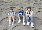 Elementary students sitting on embankment