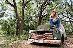 Jeune blonde cowgirl au chapeau de cow-boy assis sur camion vintage à l'extérieur