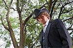 Portrait de jeune cow-boy portant le costume complet et chapeau de cowboy en plein air