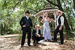 Jeunes cowboys en costumes occidentaux-jeune femme blonde en robe du soir se tenant près d'extérieur de gazebo