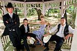 Jeunes hommes en costumes et jeune femme blonde en robe du soir assis à l'intérieur du gazebo