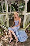 Jeune femme blonde en robe du soir et chapeau de cowboy, assis sur les marches de gazebo à l'extérieur