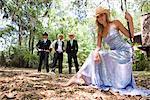 Portrait de jeune femme blonde en robe du soir et chapeau de cow-boy assis sur swing en plein air avec jeunes cowboys en arrière-plan