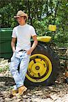 Jeune cow-boy chapeau de cowboy se penchant sur le tracteur à l'extérieur