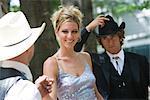 Jeunes cowboys en costumes occidentaux-jeune femme blonde en robe du soir en plein air