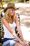 Jeune blonde cowgirl au chapeau de cow-boy, assis sur le tracteur à l'extérieur