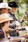 Portrait de jeunes cowboys jouant des instruments de musique en plein air