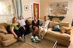Portrait de quatre amis de race blanche, assis sur le canapé dans le salon