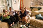 Quatre amis de race blanche assis sur le canapé griller dans le salon