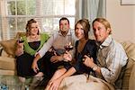 Portrait de quatre amis de race blanche assis avec des boissons sur le canapé dans le salon