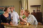 Quatre amis de race blanche assis avec boissons dans la cuisine, rire