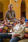 African American Teenager und älterer Mann auf einer Couch im Wohnzimmer vor dem Fernseher sitzend