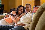 Porträt des afroamerikanischen Mutter und Teenager im Wohnzimmer vor dem Fernseher sitzen