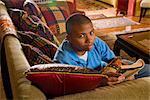 Porträt von African American Teenager Lektüre auf Couch, Blick in die Kamera