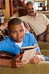 Porträt von African American Teenager Lesebuch auf Couch, Vater im Hintergrund