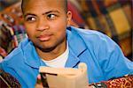 Porträt von African American Teenager Lesebuch auf Couch zu Hause, close-up
