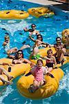 Famille et amis reposantes sur chambres à air au parc aquatique