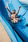Père et fils, glissant sur l'eau glissent ensemble sur chambre à air dans le parc de l'eau