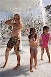 Children dancing in splashing water at water park