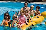 Famille et amis flottant sur chambres à air à un parc aquatique