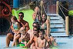 Portrait de famille jouissant sur le toboggan au parc aquatique