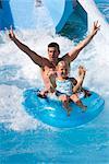 Père et fille dévaler le toboggan sur chambre à air dans le parc de l'eau