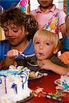 Children eating birthday cake at birthday party