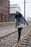 Woman Walking on Railroad Tracks in Urban Industrial Area, Portland, Oregon, USA