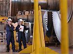 Engineers Next To Turbines