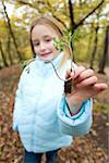 Jeune fille tenant un semis de plantes dans un bois en automne. Les racines de la plantule sont enfermés dans un petit morceau de terre et les feuilles sont développent sur les pousses vers le haut des racines.