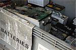 Vieilles batteries de voiture empilent dans le bac de recyclage