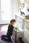Boy Looking in Open Drawer