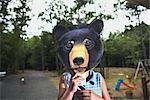 Little Girl Wearing Animal Mask in Backyard