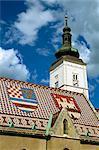 Gros plan du toit de tuiles avec motif de boucliers et de la tour de l'horloge de St. Marks church, Zagreb, Croatie, Europe