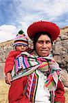Portrait d'une femme en costume traditionnel, portant son bébé sur son dos, devant les ruines Inca, près de Cuzco, au Pérou, en Amérique du Sud
