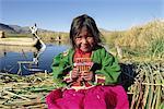 Portrait of a Uros Indian girl holding pan pipes, Islas Flotantes, Lake Titicaca, Peru, South America